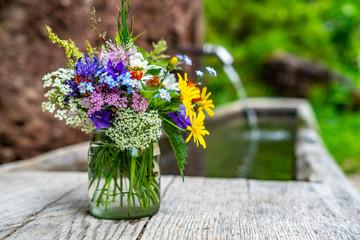 Strauß aus Wiesenblumen und Kräutern in einem Glas