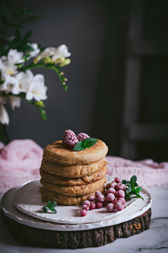 Stack of raspberry pancakes with fresh berry on porcelain plate at marble tabletop text to case with flowers over dark background