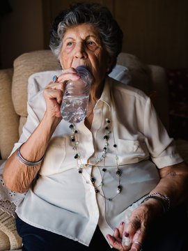 Aged curly gray haired woman in white shirt drinking pills with water from bottle sitting on armchair and looking away in apartment