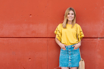 Young blonde cheerful woman standing on orange background looking at camera