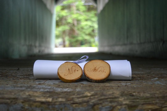 Rustic Mr. & Mrs. signs cut from tree branches sit in front of a rolled marriage license at the end of a covered wooden bridge
