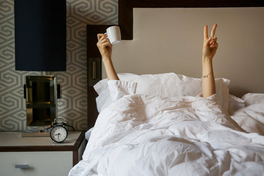 Unrecognizable  woman waking up in the morning in the bed, hiding under the blanket, holding a cup of coffee and showing the peace sign