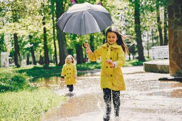 Kids in a rain coats. Children in a park. Two cute sisters