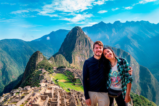 Young couple of tourist in Machu Picchu. They are together, happy and relaxed. Behind, The City of Machu Picchu and the Huayna Picchu Mountain. Archaeological site, UNESCO World Heritage
