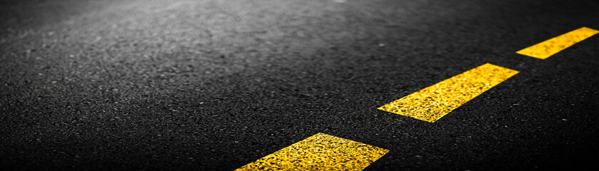 Close-up Banner Of Black Asphalt Road With Yellow Paint Lines