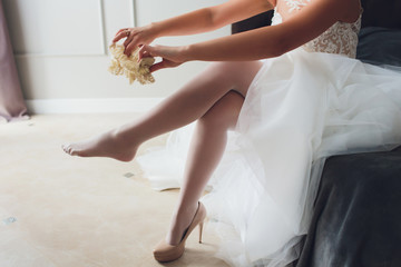 bride dresses garter on the leg. Picture of beautiful female barefoot legs in wedding dress. Bride dresses stockings on feet. Bride putting a wedding garter on her leg.