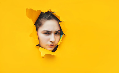 Funny teenage girl peeping through hole on yellow paper. The concept of surprise, sad mood from what he saw. Suspicion, skepticism, seriousness, piercing eyes. Copy space.