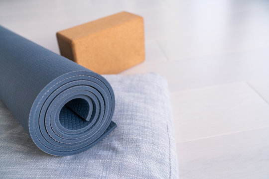 Yoga mat, cork block and linen meditation cushion. Natural organic material props for wellness studio on wooden floor background. Eco-friendly sustainable products for wellness and fitness.