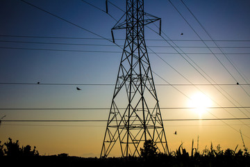 A silhouetted steel power tower at sunset