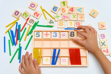 kid doing addition equation using counting rods