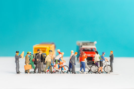 Miniature toys of crowd walking on zebra crossing with vehicles stopped concept.