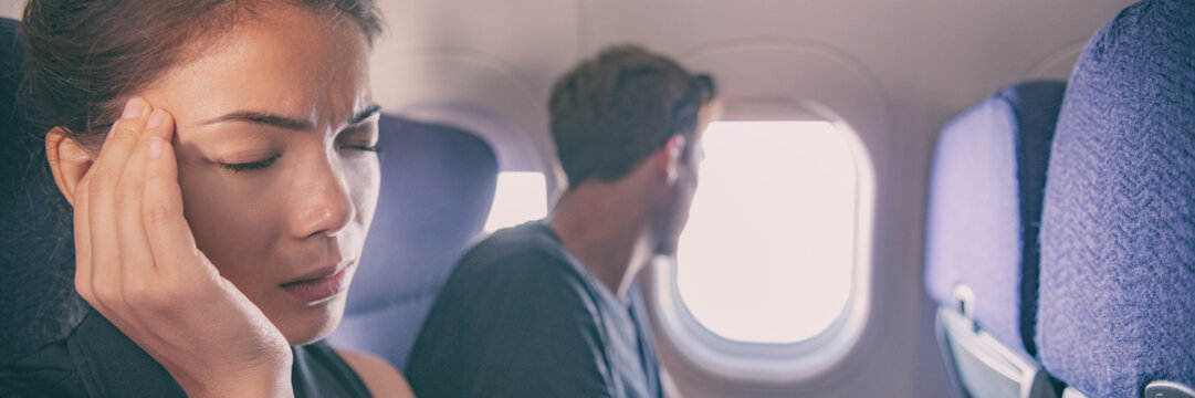 Sick fear of flying inside plane cabin woman in airplane with headache panoramic banner. Asian passenger on travel feeling sick with stress anxiety migraine. Couple tourists.