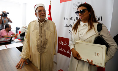 Abdel Fattah Morou, vice-president of the moderate Islamist party Ennahda stands next to his daughter, as he presents his candidacy for the presidential elections, in Tunis