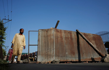 A Kashmiri man walks past a blockade put up by residents to prevent Indian security force personnel from entering their neighborhood during restrictions, in Srinagar