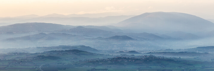 A panoramic view of Umbria valley with hills and mist