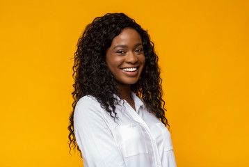 Cheerful african american girl over yellow background
