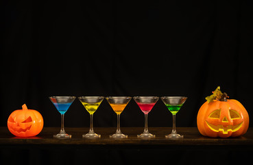 Halloween pumpkin and wine glass on the black background prepare to celebrate on Halloween