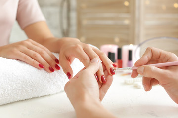 Woman getting professional manicure in beauty salon, closeup