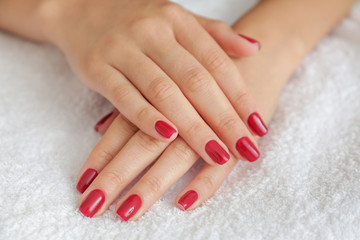 Poster de jardin Manicure Manicured hands of young woman on towel, closeup