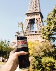 diet coke held in front of the Eiffel tower