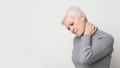 Senior woman suffering from neck pain and feeling exhausted