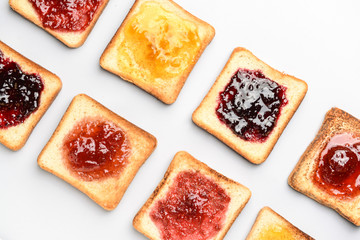 Tasty toasted bread with different jams on white background