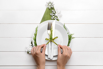 Female hands and beautiful table setting for Christmas dinner on white wooden background Wall mural