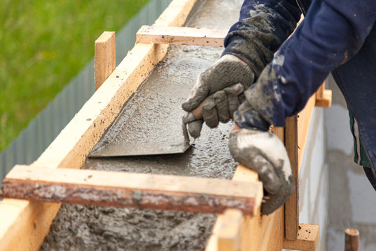 Worker levels concrete in formwork using a trowel