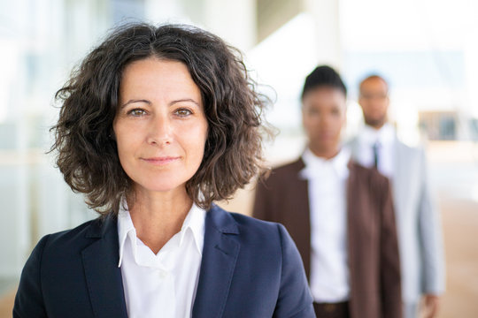 Successful female leader posing with her team in blurred background. Middle aged businesswoman smiling at camera, her two colleagues standing behind her. Successful team leader concept