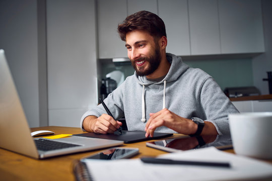 Cheerful young graphic desginer working late from home