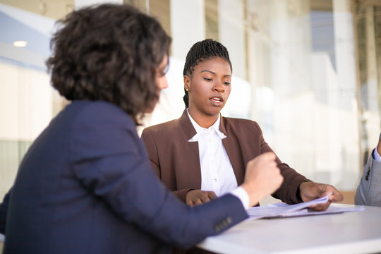 Confident female professional explaining document details to colleagues Multiethnic business man and women sitting at table and checking papers. Paperwork concept