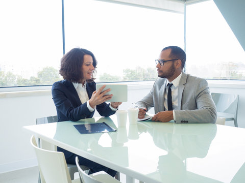 Female mentor training male newcomer. Focused business man and woman sitting at meeting table, using tablet, showing and looking at screen and taking notes. Mentorship concept