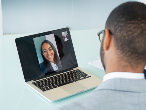 Happy business team talking through video call. Male office employee sitting at laptop, his young female colleague smiling from computer screen. Communication concept