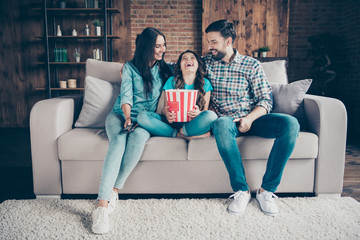 Portrait of cheerful little girl with wavy hair laugh in lotus position and parents wearing denim jeans checkered shirt sit divan in house indoors