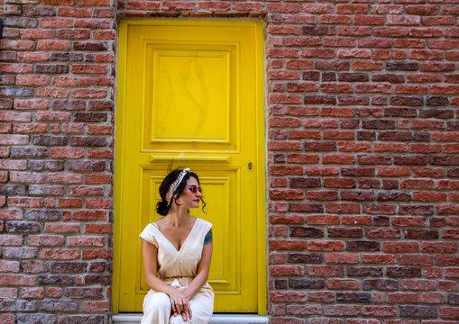 woman sitting on yellow door and orange brick wall in Istanbul in Turkey