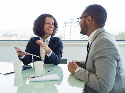 Joyful corporate trainer telling newcomer about work in company. Happy business woman holding tablet and talking to male colleague at meeting table. Newcomer concept