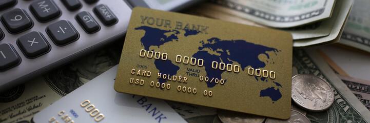 Credit card and calculator lying on big amount of US money closeup Fototapete