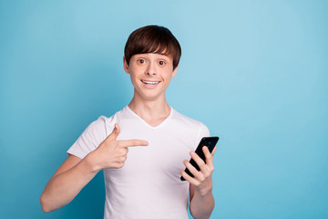 Photo of boy having been told to sell phone he is pointing at while isolated with blue background