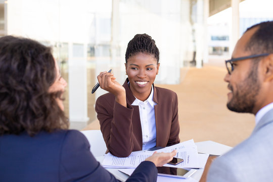 Happy African American business woman discussing deal with partners. Multiethnic business partners sitting at table with documents in outdoor cafe and talking. Partnership concept