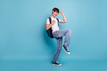 Full length body size photo of dancing rejoicing overjoyed cheerful guy having won olympiad games at math at school while isolated with blue background