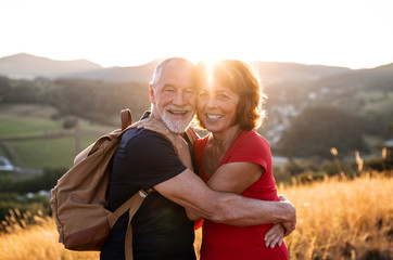 Senior tourist couple travellers with backpacks hiking in nature, hugging. Wall mural