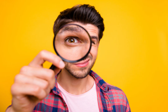 Photo of amazed man trying to see microorganisms with loupe but he evidently cannot manage to do it while isolated with yellow background