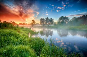 Beautiful summer sunrise over river banks