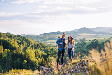 Fototapeta Young tourist couple travellers with backpacks hiking in nature, resting. obraz