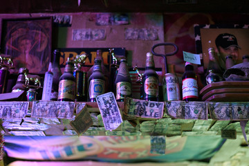 Dollar bills signed by past customers are seen at The Field Office bar in Midland