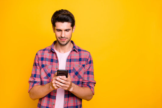 Photo of man focusing on chatting with something mysterious while isolated with yellow background