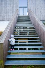 little baby girl climbing upstairs