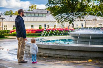 father and daughter watching the fountain