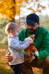 father and daughter playing with toy fox