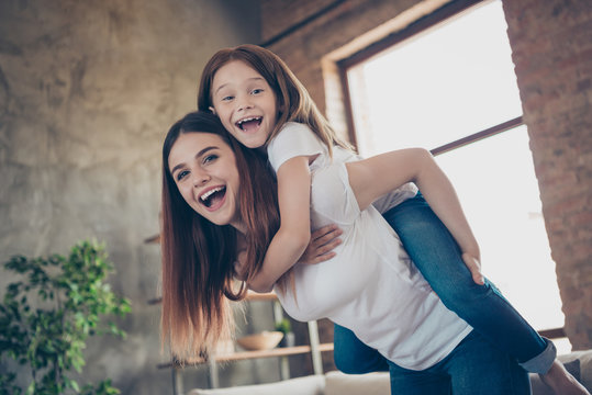 Portrait of cheerful lovely mommy kid laughing piggybacking wearing white t-shirt denim jeans in big house indoors